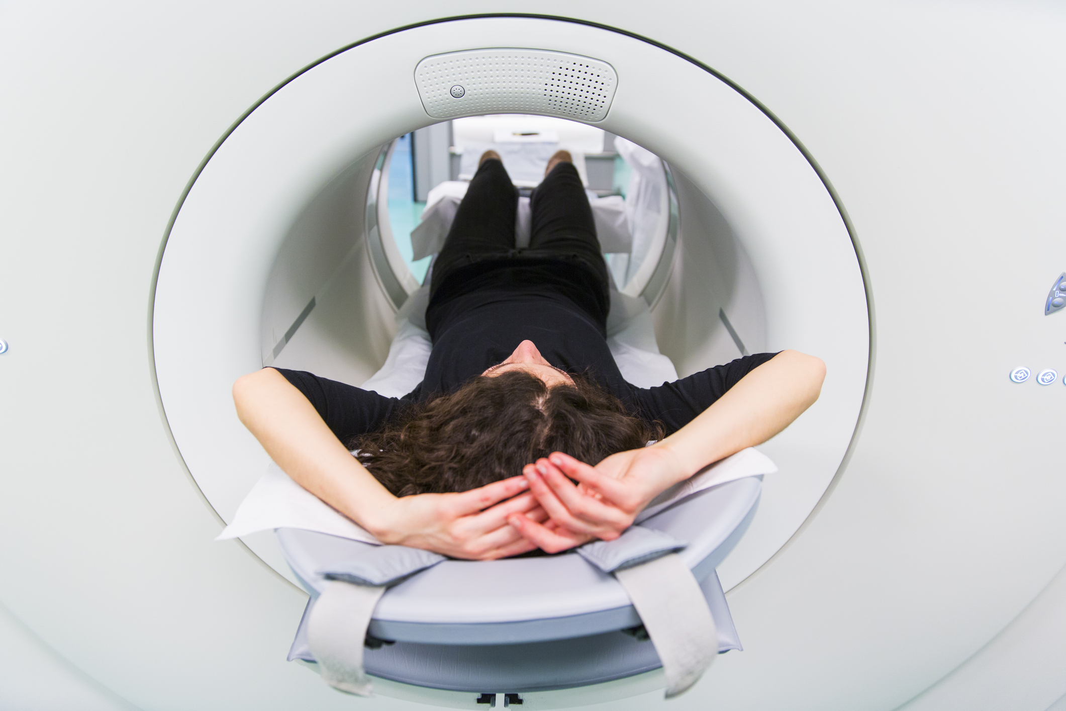 A lady lying in a cylindrical PET scanner