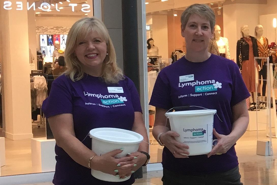 Two females holing Lymphoma Action collection buckets