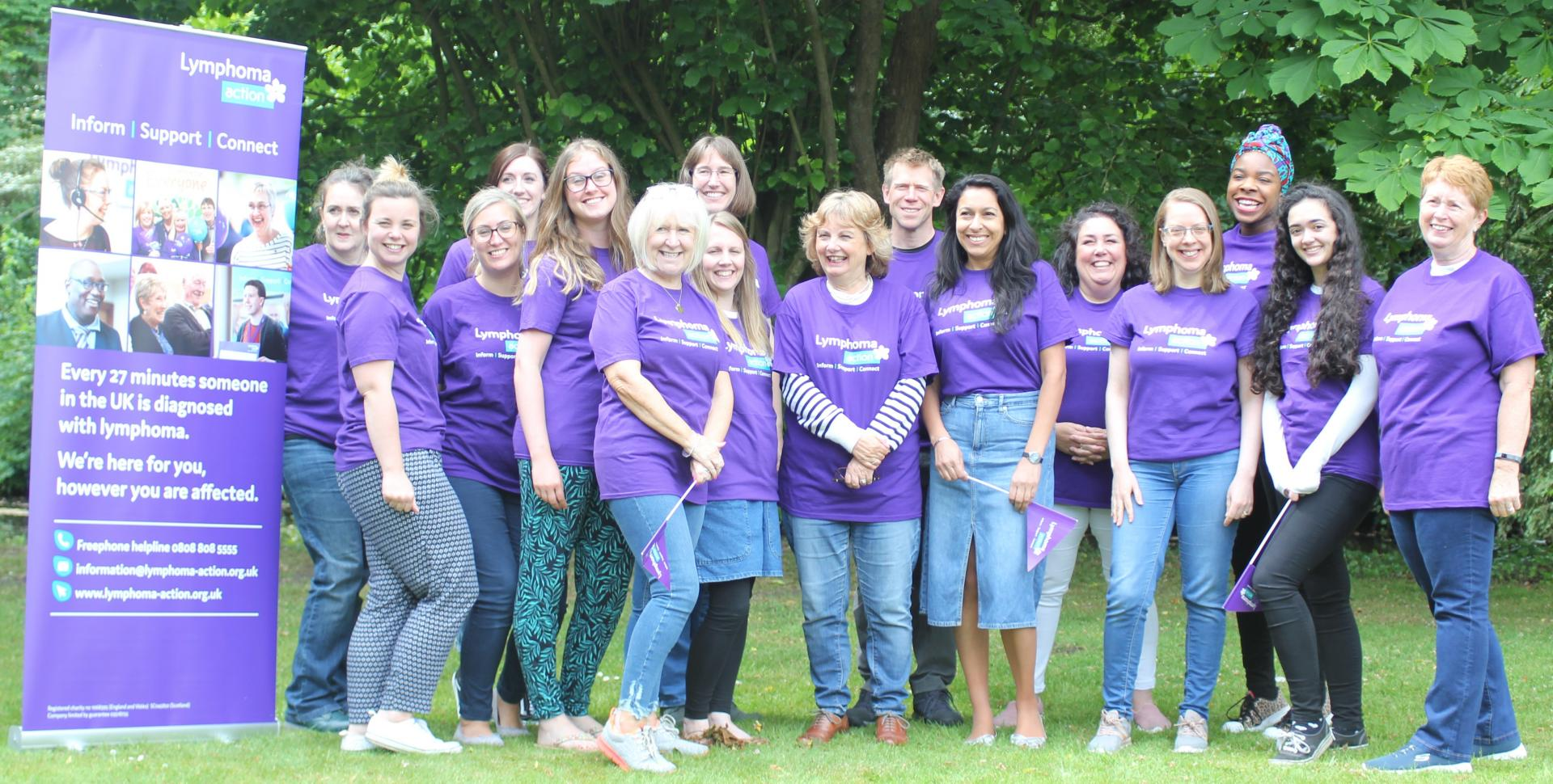 Group of staff in purple t-shirts smiling