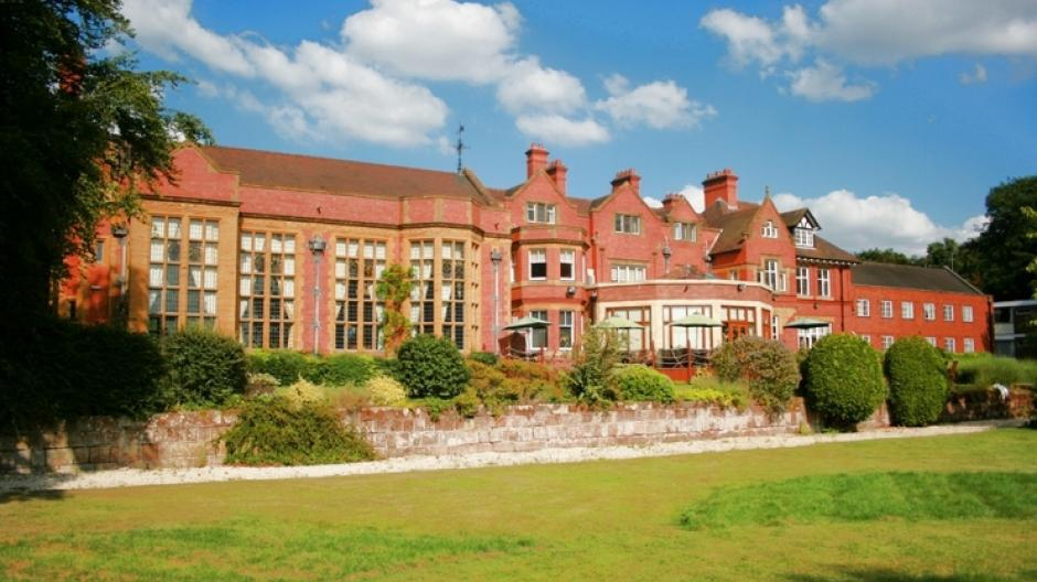 Panoramic view, red bricked building and vibrant green lawn