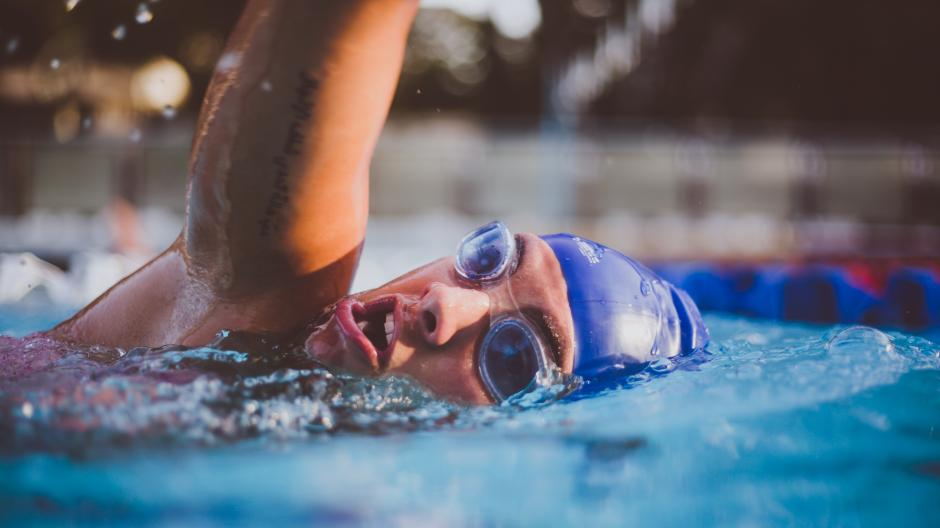 person swimming in goggles and swimming hat